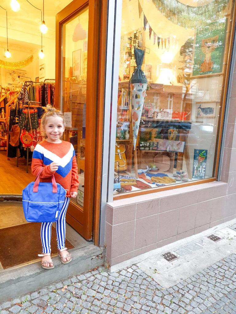 Ein kleines Mädchen steht im Eingang von dem Heimatkinder-Laden mit einem blauen Korb und lächelt in die Kamera