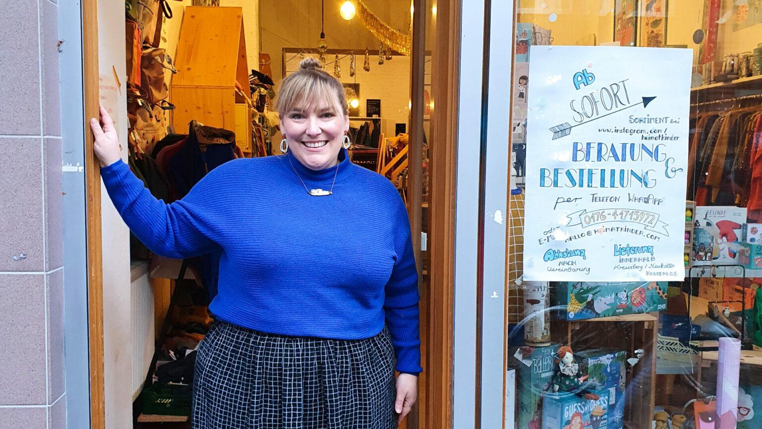 Die Inhaberin Suse steht im Rahmen der Tür von ihrem Laden